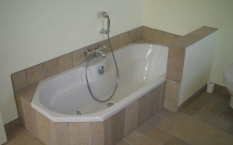 Muret badekar med fliser i beige